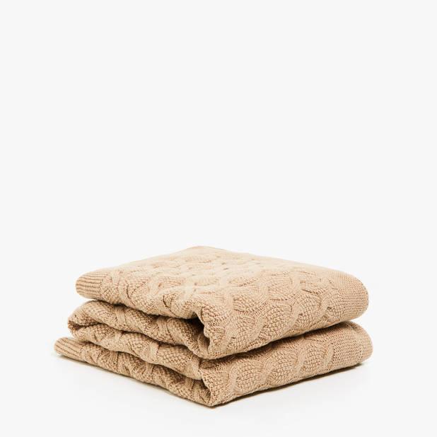 Cette couverture en laine faite en tricot torsadé est un objet utilitaire et de décoration. Zara Home, 89,99€
