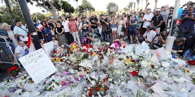 TOPSHOT - People gather around a makeshift memorial to pay tribute to the victims of an attack in the French Riviera city of Nice on July 15, 2016, a day after when a man rammed a truck through a crowd celebrating Bastille Day, killing at least 84 people. / AFP PHOTO / Valery HACHE
