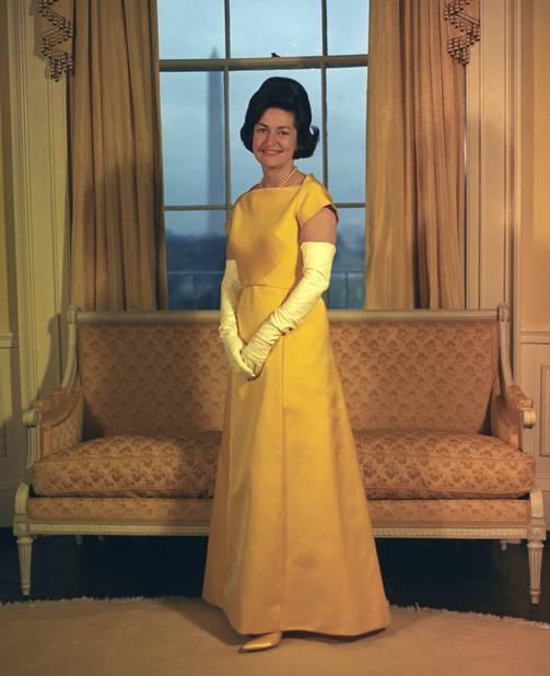 En 1965, Lady Bird Johnson apparaissait très guindée dans sa longue robe jaune avec des gants assortis.