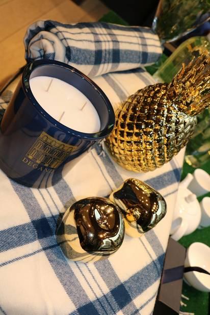 Chez Degand : Bougie Ambre de la Maison Degand, 3 mèches, combustion time 120 heures 100 euros - Ananas porcelaine OR décoration, hollande 65 euros pièce- Set de 2 pommes OR décoration, hollande 25 euros - plaid bleu et blanc à carreaux lambswool 250 euros
